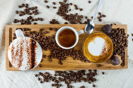 Selection of types of coffees on a wooden board  frothy cappuccino with cocoa on top, espresso and latte