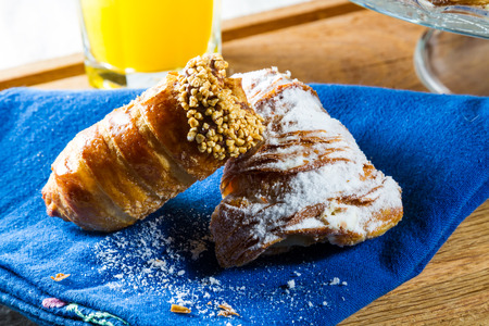 sugarcoated: Typical continental breakfast with sugar-coated cannoli and croissants filled with custard. Stock Photo