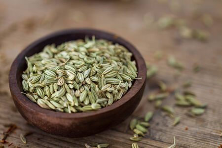 fennel seeds: Fennel seeds in a small wooden bowl on an old wooden table. Stock Photo