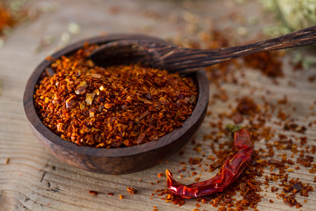 fragrant scents: Wooden bowl full of fiery chilli pepper flakes.