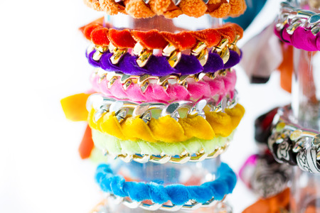 fad: Fashion accessories: very colourful bracelets made by weaving velvet ribbons and metal chains together. White background. Copy space. Stock Photo