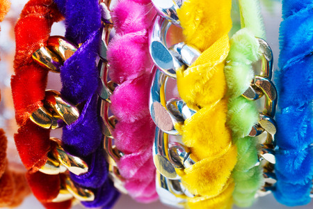 Fashion accessories: very colourful bracelets made by weaving velvet ribbons and metal chains together. photo