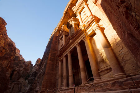 siq: Facade of the Treasury, one of the main monuments in Petra, Jordan, reached after a long walk through a canyon (called siq).