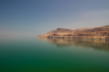 landlocked: The green water of the land-locked Dead Sea in Jordan, by the entrance to Wadi Mujib, on the Jordan side. The Israeli coast in the distance. Stock Photo