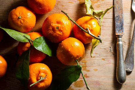 zesty: Juicy, fresh clementines against a wooden background.