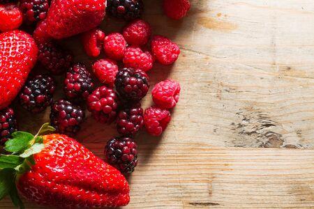 Frutti di bosco: fragole, lamponi e more su sfondo di legno .. colazione cibo sano.