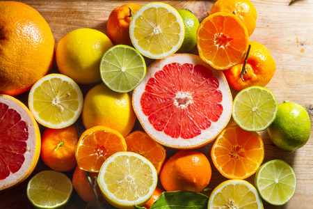 cooking ingredients: Fresh, juicy, zesty citruis fruits: lemons, limes, grapefruit, clementines. Against wooden background.