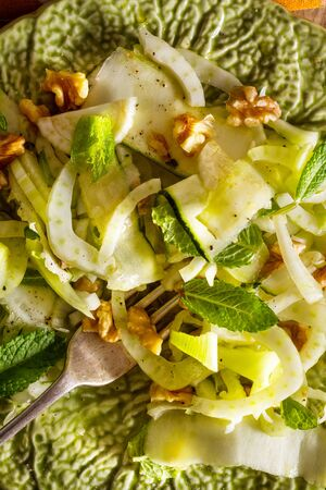 Healthy eating: raw fennel salad with walnuts, raw courgettes, mint leaves and lemon juice. Zesty, fresh, summery and light food. Perfect for a diet.