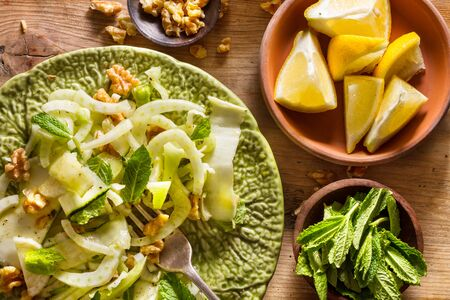 zesty: Healthy eating: raw fennel salad with walnuts, raw courgettes, mint leaves and lemon juice. Zesty, fresh, summery and light food. Perfect for a diet.