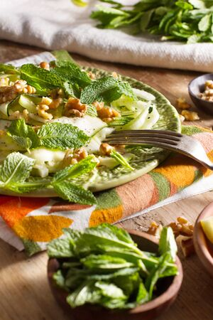 summery: Healthy eating: raw fennel salad with walnuts, raw courgettes, mint leaves and lemon juice. Zesty, fresh, summery and light food. Perfect for a diet.