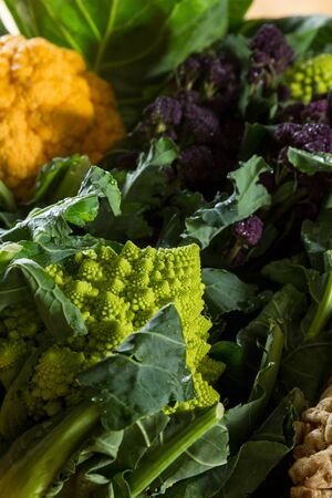 sequences: Romanesco cauliflower with its fractal shapes and Fibonacci sequences in focus, with purple broccoli and yellow cauliflower in the background.