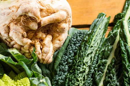swede: A big swede, vegetable from the Brassicaceae family, with black cabbage leaves and Romanesco cauliflower in the frame.