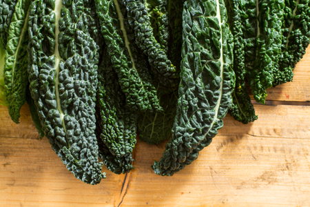 cruciferous: Fresh and dewy black cabbage leaves on a wooden background. Stock Photo