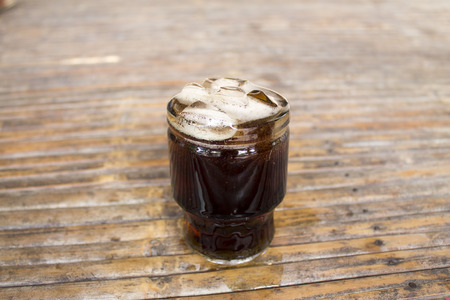 Cola with ice cubes in glass on bamboo table