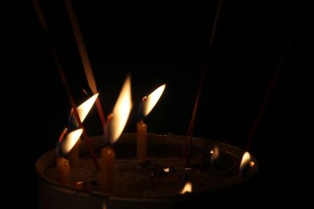 candles burning brightly on black background