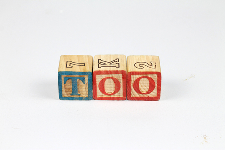 Wooden alphabet blocks spelling out TOO on white background. Colorfull wooden alphabet blocks. 版權商用圖片