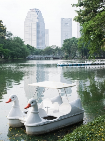 A white swan boat parks in a lake in city public park. Stock Photo