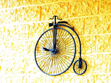 A bicycle of big and small wheels is  decorated on a wall