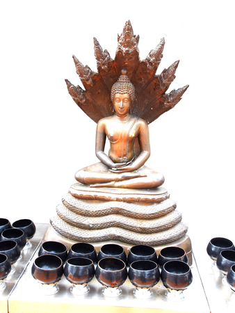 The Buddha statue style sitting meditation with serpent cobra hood spread behind his head covered  This is the Buddha for those born on Saturday                                                                                                              Stock Photo