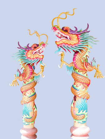 Two replicas of Chinese dragon spiralling over  long poles  Stock Photo