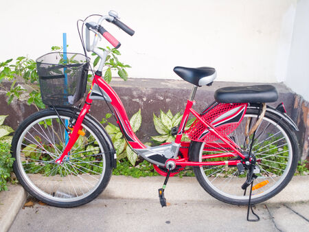 A red bicycle with a front basket for carrying stuff