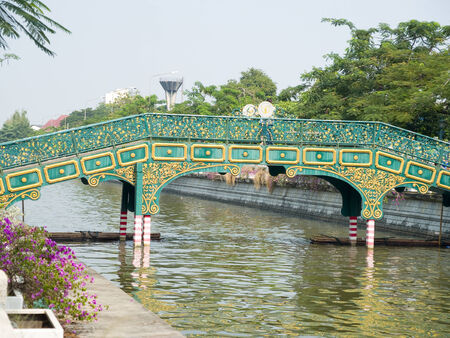 A green canal bridge with golden designs  cross a canal in the inner city of Bangkok