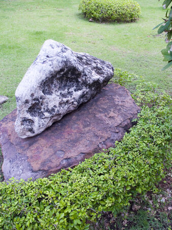 One rock is on top of another in a garden