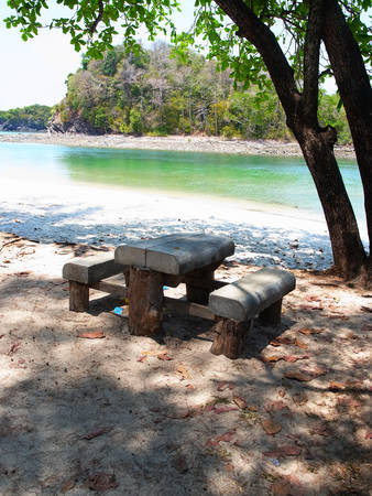 whether: Wooden seats and tables stand on white sand beach and always be there whether it is rainy or sunny.