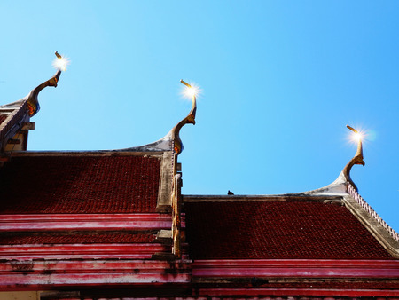 sloping: Glistening gable  apex and toothlike ridges on the sloping edges of  roof tops of a Thai temple. Stock Photo