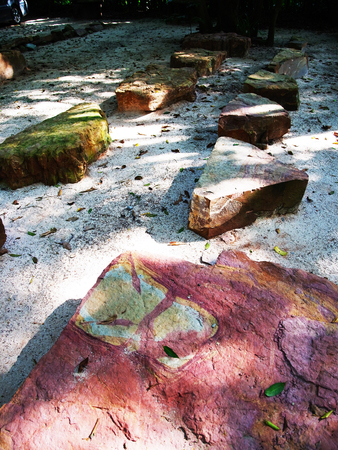 footpath: A simple footpath made from colorful stony slabs on sand.