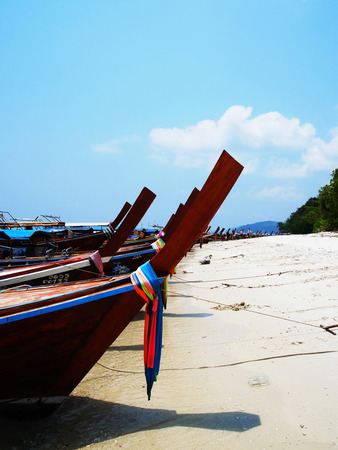 upright row: A row of fishing boats modified to be traveling boats on sandy beach. Stock Photo