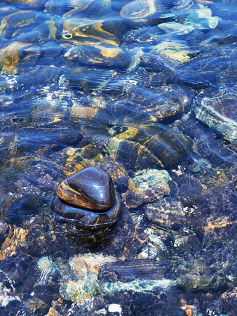 glistening: A part of round , black and glistening stones on Hin Ngam island , Tarutao National Park, Thailand.