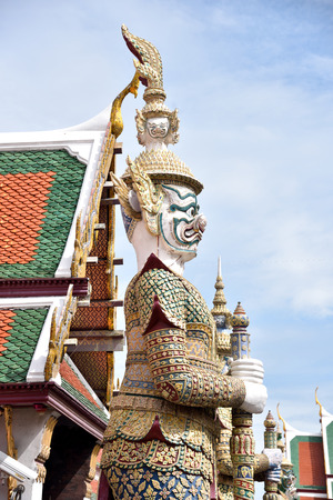 guarding: The white giant statue called Chakrawat with four faces stands guarding a temple gate in Wat Phra Kaeo , Thailand. Stock Photo