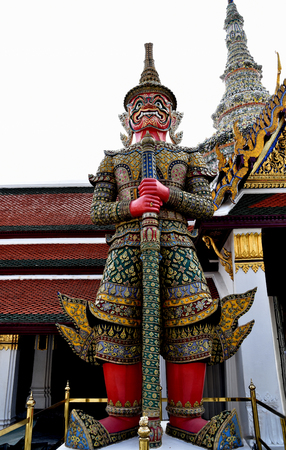 guarding: The red giant statue called Suriyaphop is standing guarding the temple gate of Wat Phra Kaeo , Thailand.