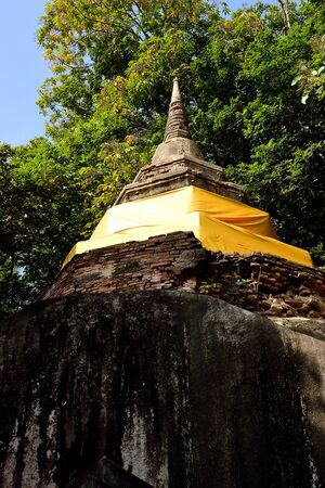 The ancient pagoda situates on the big rock with a high cliff below.This picture was taken from Wat Phra Dhat Pha - Ngao , Chiang Saen , Chiang Rai Province , Thailand.