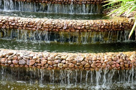 tiers: Artificial waterfalls fall from tiers of rocks to form small water curtains. Stock Photo
