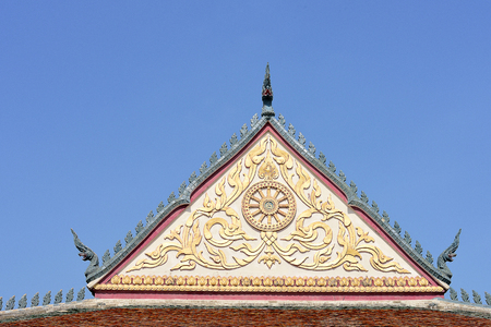 serpents: The gable of a temple decorated with serpent sculptures , Thai design , and enblem of wheel of life.