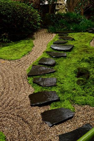 raked: Raked gravel surrounding steppingstones in a small japanese garden.