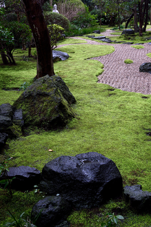 uniquely: Japanese garden is uniquely  designed to blend various elements  that have their distinct significance.Those elements are rocks , moss , path , plants and others. Stock Photo
