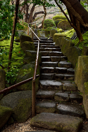 The staircase made from stony steps with bamboo rails in a Japanese garden.