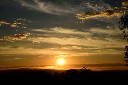 暗い灰色がかった空に曇りと黄金水平線の下太陽の消失の風景。
