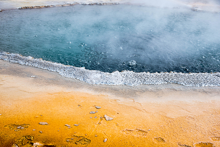The superheated  and intensely blue colored waters of Crested Pool Hot Spring in the Upper Geyser Basin in  Yellowstone National Park . This picture was taken in May , 2016.