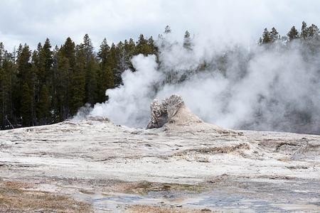 A very large cone - type geyser erupts sporadic eruptions  above the 12 feet tall geyserite. Stok Fotoğraf