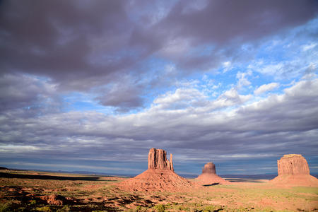 The scenic view of the Mittens in Monument Valley against cloudy sky.