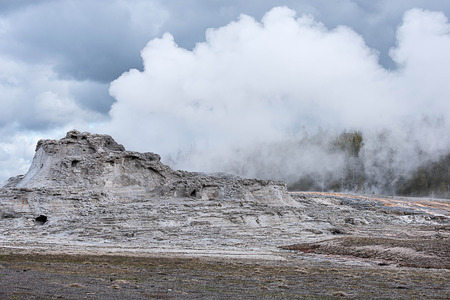 The eruption of Castle Geyser that can be predictable and has turned part of a pine forest to be a thermal desert. Stock Photo