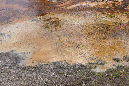 A hot - spring area with colorful features of mineral deposit and microbial mat.