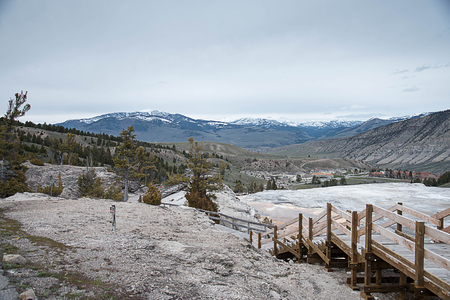 The landscape of Mammoth Area with a wooden boardwalk across geothermal area and snow - capped mountains as a background.