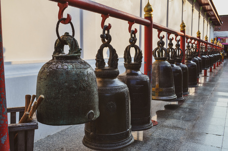 Aged bells hanging on red steel bar over marble floor with wooden stick for buddhist who would like to knocking the bell for worship as thai traditional at Buddhism temple in Thailand.