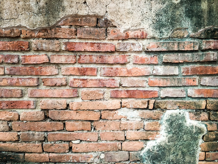 An aged, cracked and chipped stucco wall with an area of exposed brown brick. Brick wall background texture. Stock fotó