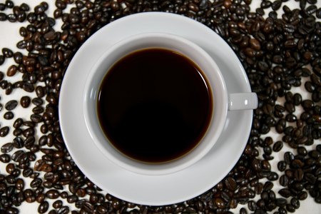 Black coffee in white cup on white saucer and coffee beans on white background. A cup of coffee.